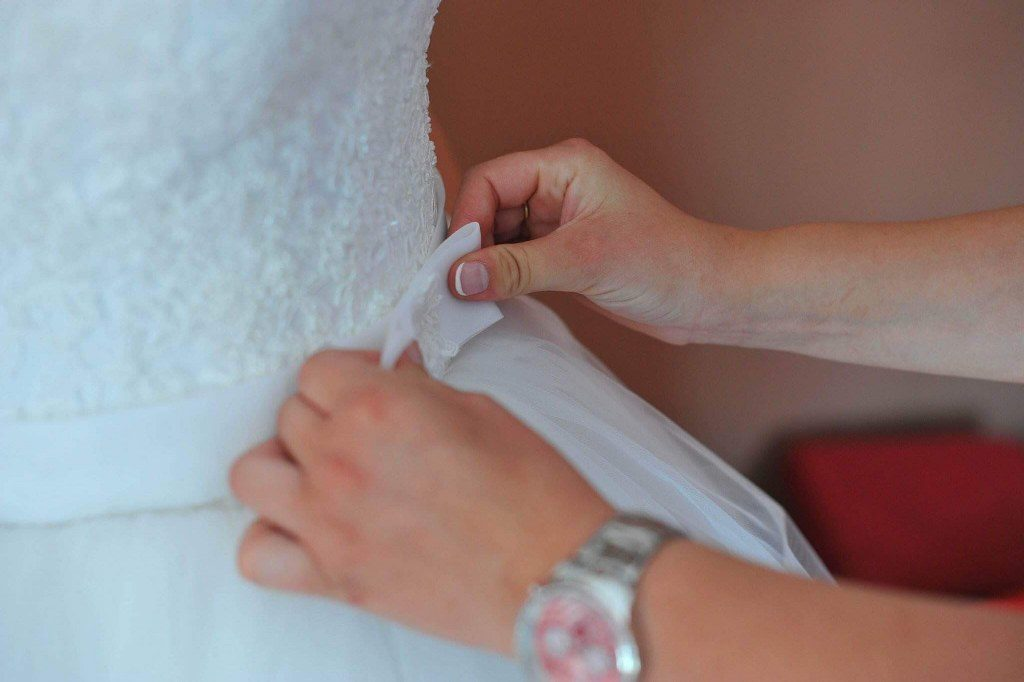 Bride Helping Groom Dressing Up for Wedding Ceremony